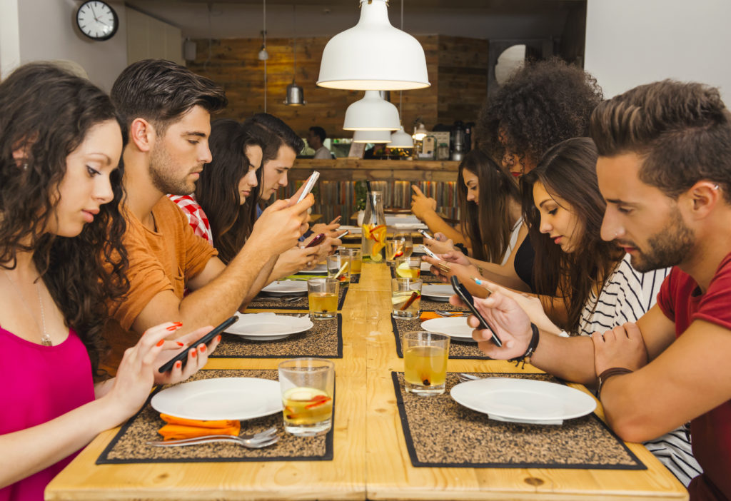 Customers Using Phones At Tables